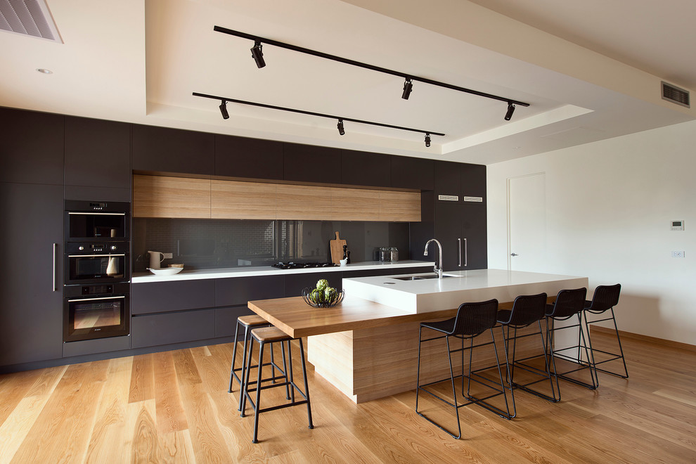 Contemporary kitchen design with black cabinets and light island.