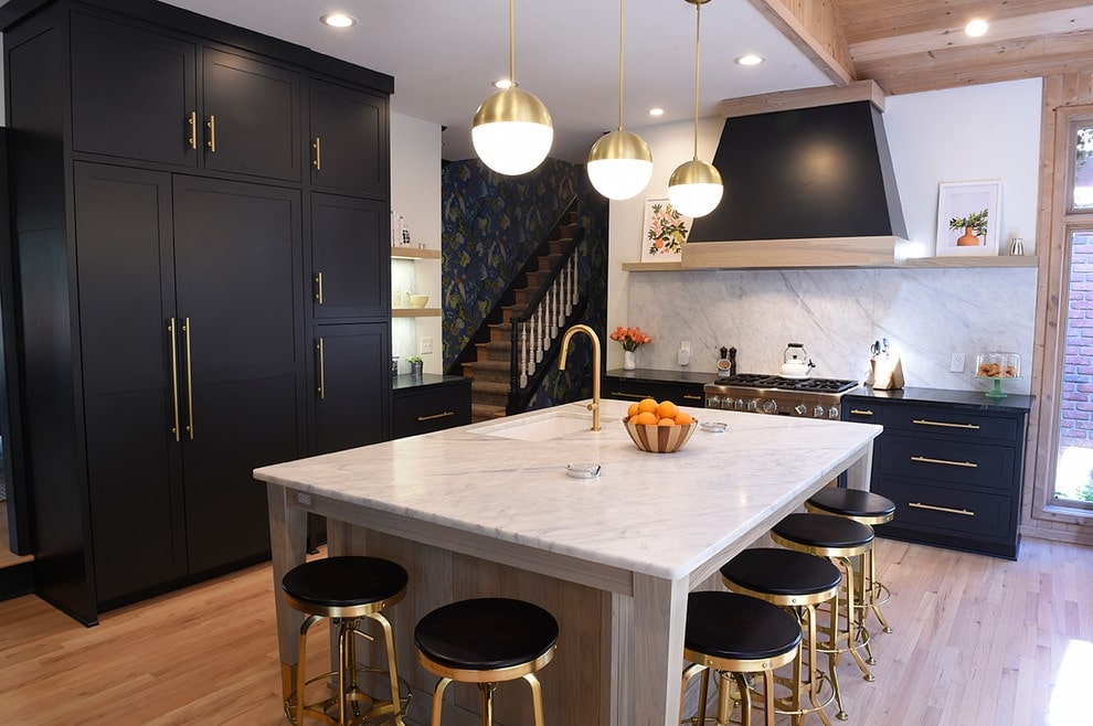 Stunning contemporary kitchen with black cabinets, marble island countertop, and copper light fixtures. Design by Hurst Design Build Remodeling